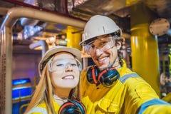 Homem e mulher em um uniforme amarelo, em vidros, e em capacete do trabalho em um ambiente industrial, em uma plataforma petrol?f imagens de stock