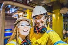 Homem e mulher em um uniforme amarelo, em vidros, e em capacete do trabalho em um ambiente industrial, em uma plataforma petrol?f imagens de stock royalty free