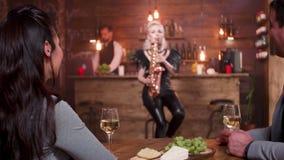 Homem e mulher em uma data romântica que escutam um concerto vivo do jazz video estoque