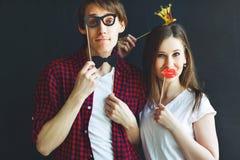 Homem e mulher engraçados dos pares com coroa, laço e bordos fotografia de stock royalty free