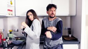 Homem e mulher engraçados nos pijamas na cozinha que olha a dança bebendo do café da câmera feliz vídeos de arquivo