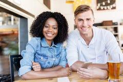 Homem e mulher felizes com o smartphone na barra Fotografia de Stock