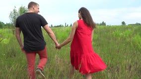 Homem e mulher gravida bonitos dos pares com cabelo longo em um vestido vermelho Família video estoque