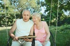 Homem e mulher idosos de sorriso 65-69 anos absorbedly de readi velho Imagem de Stock Royalty Free