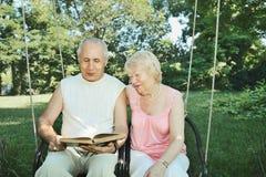 Homem e mulher maduros de sorriso 65-69 anos de leitura velha um livro dentro Imagem de Stock Royalty Free