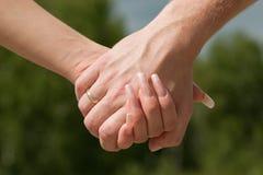 Homem e mulher a manter-se para as mãos. Imagem de Stock