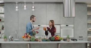 Homem e mulher na manhã que beijam-se e que fazem o batido para o café da manhã na cozinha moderna, bebidas do homem video estoque