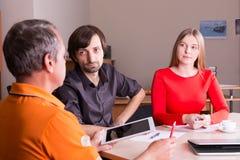 Homem e mulher na reunião com o chefe Imagem de Stock