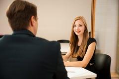Homem e mulher na reunião de negócios, sentando-se no escritório, disco Imagens de Stock Royalty Free