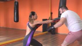 Homem e mulher nas luvas de encaixotamento que enganam ao redor no gym, encaixotamento video estoque