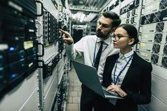 Homem e mulher no centro de dados foto de stock
