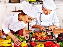 Homem e mulher no chapéu do cozinheiro chefe que cozinham a galinha Foto de Stock Royalty Free