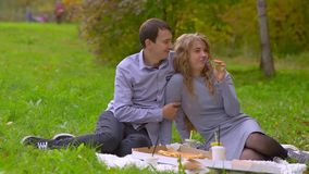 Homem e mulher no parque no gramado, descanso, aspirando uma flor vídeos de arquivo