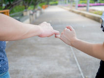 Homem e mulher no relacionamento que cruza o dedo mindinho como prometido Fotos de Stock Royalty Free