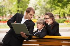 Homem e mulher novos de negócio que usa o portátil no parque Fotografia de Stock