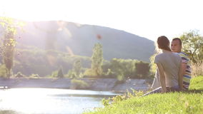 Homem e mulher perto da água no banco de rio. vídeos de arquivo