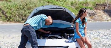 Homem e mulher perto de seu carro quebrado foto de stock