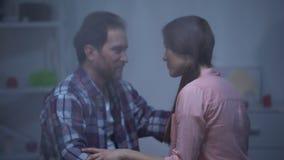 Homem e mulher que abraçam na sala no dia chuvoso, reconciliação após a discussão vídeos de arquivo