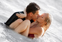 Homem e mulher que beijam no mar Imagens de Stock