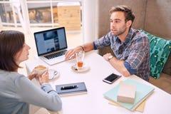 Homem e mulher que conduzem uma reunião de negócios no café local Imagens de Stock Royalty Free