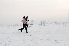 Homem e mulher que correm na neve fotografia de stock