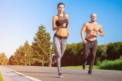 Homem e mulher que correm no parque imagens de stock