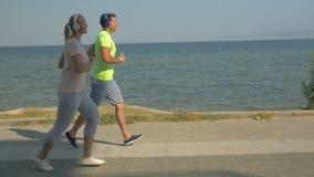 Homem e mulher que correm no pavimento ao lado do mar video estoque