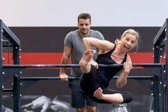 Homem e mulher que dão certo em barras transversais em um gym imagem de stock