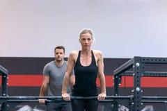 Homem e mulher que dão certo em barras transversais em um gym fotografia de stock
