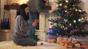 Homem e mulher que decoram a árvore de Natal na sala moderna A menina dá brinquedos, homem que pendura os em ramos Pares felizes filme