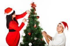 Homem e mulher que decoram a ?rvore de Natal Fotos de Stock