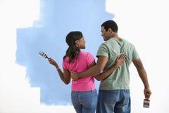 Homem e mulher que discutem o trabalho da pintura. Imagem de Stock