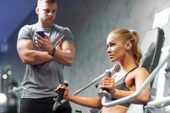 Homem e mulher que dobram os músculos na máquina do gym Imagem de Stock