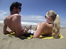 Homem e mulher que encontram-se na praia Fotografia de Stock Royalty Free