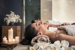 Homem e mulher que encontram-se para baixo em camas da massagem no cente asiático do bem-estar foto de stock