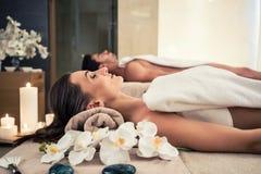Homem e mulher que encontram-se para baixo em camas da massagem no centro asiático do bem-estar fotografia de stock royalty free