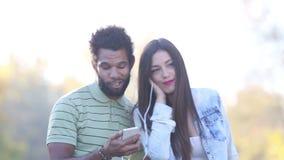 Homem e mulher que escutam a música junto, compartilhando de fones de ouvido video estoque