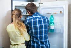 Homem e mulher que estão o refrigerador próximo na cozinha fotos de stock royalty free