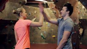 Homem e mulher que exercitam no gym de escalada interno filme