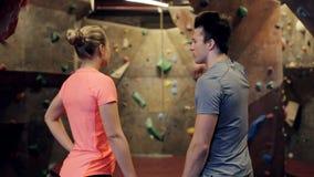 Homem e mulher que falam no gym de escalada interno filme
