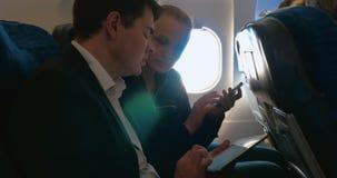 Homem e mulher que falam no negócio usando a almofada video estoque