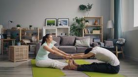 Homem e mulher que fazem esticando os exercícios que guardam as mãos que sentam-se em esteiras em casa filme