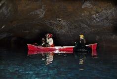 Homem e mulher que fotografam Lava Tube Lake Cave interno Imagens de Stock