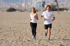 Homem e mulher que funcionam na praia fotografia de stock