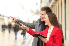 Homem e mulher que guardam uma tabuleta que aponta afastado na rua fotografia de stock royalty free