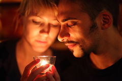 Homem e mulher que mantêm a vela de vidro. Imagens de Stock