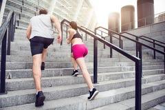 Homem e mulher que movimentam-se nas escadas Foto de Stock Royalty Free