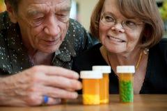 Homem e mulher que olham medicamentações da prescrição Fotografia de Stock Royalty Free