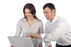 Homem e mulher que olham o portátil e o riso Foto de Stock Royalty Free