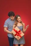 Homem e mulher que olham o telefone com um presente no estilo Pin Up mim fotografia de stock royalty free